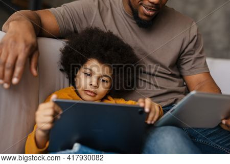 Black father and son using tablet computers while sitting on sofa at home
