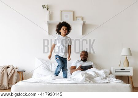 Black boy making fun on bed while his father using tablet computer at home