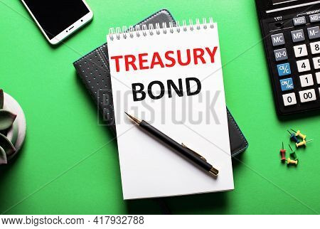 On A Green Background - A Telephone, A Calculator And A Diary With The Inscription Treasury Bond