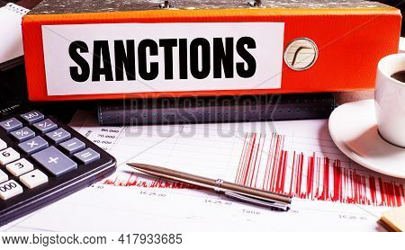 The Red Document Folder Says Sanctions Next To The Coffee, Calculator And Pen.