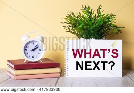 What Is Next Is Written In A Notebook Next To A Green Plant And A White Alarm Clock, Which Stands On