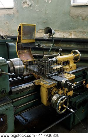 Front View Of An Old Metal Lathe In A Lathe Shop. The Lathe Components And The Spindle.