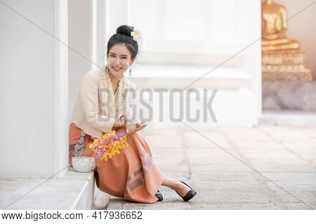 Attractive Thai Woman In An Ancient Thai Dress Holds A Fresh Flowers Paying Homage To Buddha To Make