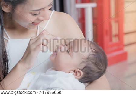 A Beautiful Asian Woman Holds Her Newborn Daughter Who Sleeps Lovingly And Cherishes And Brings Up H