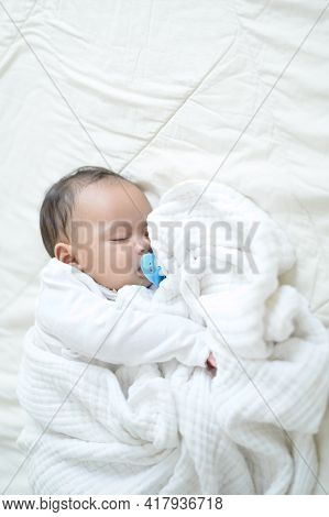 A Recently Born Half-born Baby Is Wrapped In A White Cloth And Slept In Bed While Sucking On A Rubbe