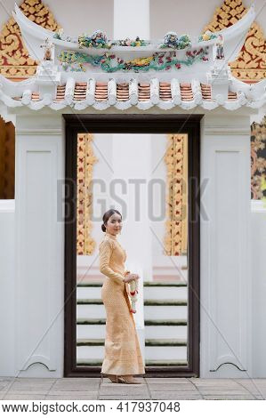 A Graceful Thai Woman In Thai Dress Adorned With Precious Jewelry Holds A Flower Garland Through The