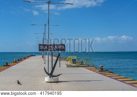 The Pier From Isla Mujeres With The Signe, Background The Sea And Cancun, Mexico.
