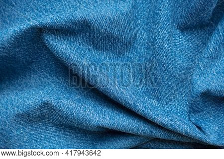 Blue Jeans Cotton Fabric Crumpled Effect Denim Texture Background. Jean Textile Fold Wrinkle Crease
