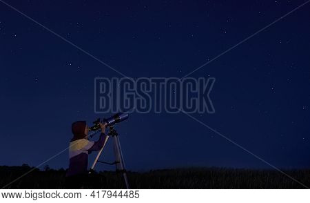 Telescope And Stars. Woman Looks Through An Optical Telescope At A Starry Sky. Stargazing, Night Sky