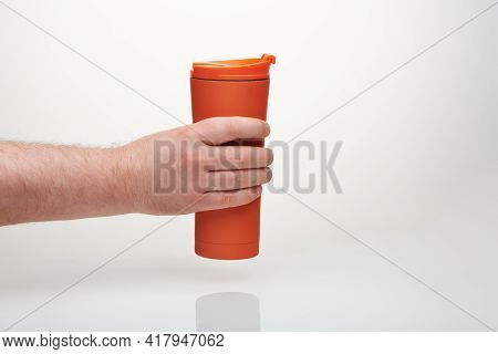 Brutal Man Hand Holds Orange Travel Mug. Reusable Coffee Cup To Go. Thermos Stainless Steel Bottle W