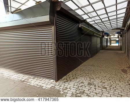 Alleyway Of Closed Shutter Of Shops In The Market During Winter. Shutdown Or Lockdown Out Of Busines