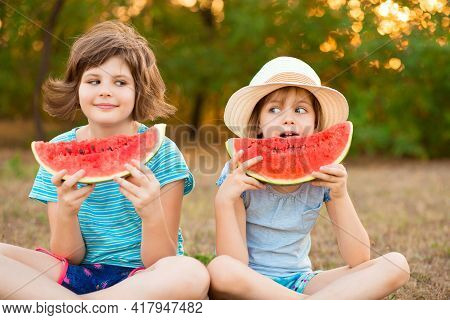 Two Preschool Smiling Child Sister Sit With Crossed Legs On Grass And Eating Watermelon At Summer Pa