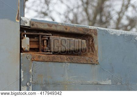 Part Of An Iron Dirty Side Of A Truck With A Large Brown Latch In Rust