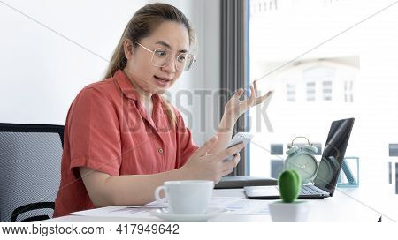 Asian female employee talking on the phone and working in a laptop with a Shock face, Office staff w