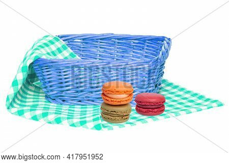 Closeup Of A Empty Wicker Basket And Three Macaron On A Green White Checkered Napkin, Blanket Or Tab