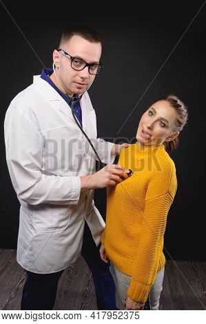 A Young Doctor With Glasses Listens To The Heartbeat Of A Woman Making Faces. Medical Humor. False D