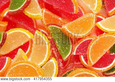 The Background Is Made Up Of A Variety Of Delicious Sweet Colored Marmalades In The Form Of Fruit Sl