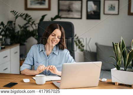 Young Pretty Woman Talking On Video Call And Waving Hand While Sitting At Table In The Homeoffice Ro