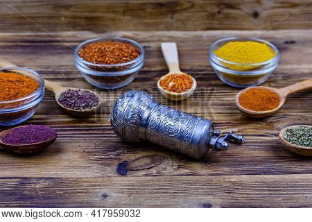 Spoons And Bowls With Oriental Spices And Spice Mill On Wooden Table