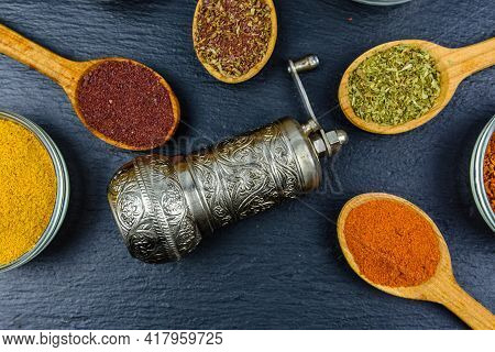 Spoons And Bowls With Oriental Spices And Spice Mill On Slate Board. Top View