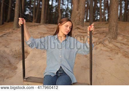 Romantic Young Woman On A Swing Over Lake At Sunset. Young Girl Traveler Sitting On The Swing In Bea
