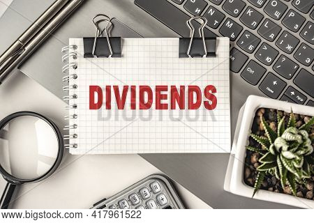 Dividends Text On A Notepad And Laptop, Office Tools. Business, Financial Concept. Remote Training.
