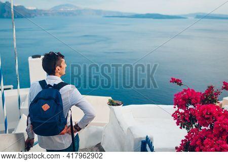 Santorini Island Traveler Man Enjoying Caldera View From Oia, Greece. Traditional White Houses With