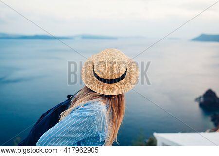 Tourist Woman Walking On Santorini Island, Greece Enjoying Sea Landscape. Traveler With Backpack Enj