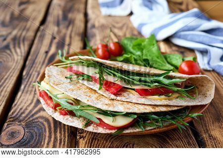 Piadina Romagnola With Mozzarella Cheese, Tomatoes, Ham And Rocket Salad On Wooden Table. Italian Fl