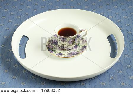 A White Plastic Tray With A Cup Of Black Tea Stands On A Blue Tablecloth. Closeup