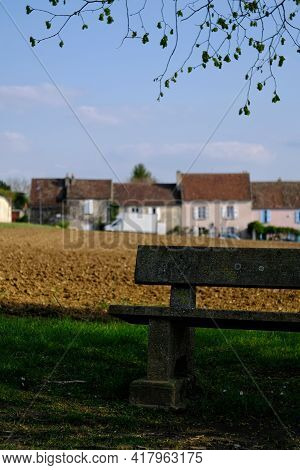 A Lonely Bench And A Small Village In The Background In France