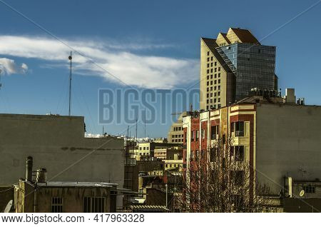 View Of The Roofs Of Densely Built-up Tehran With A View Of A High-rise Building With A Blue Glass F