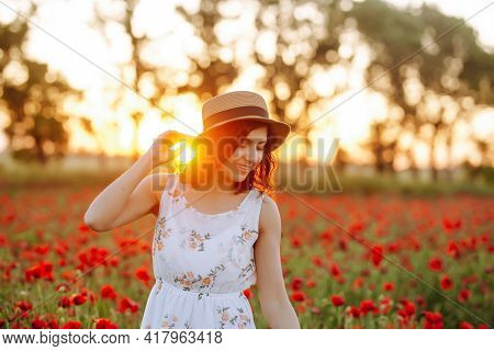 Portrait Of A Girl In A Poppy Field Against A Sunset Background. Sunny Photo Of A Woman In A Straw H
