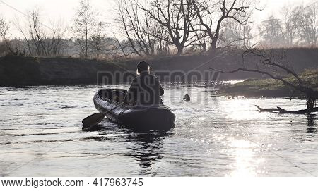 A Man Sailing The River In The Late Of Afternoon