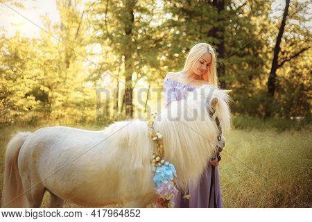 Woman In Purple Dress Hugging White Unicorn Horse. Dreams Come T