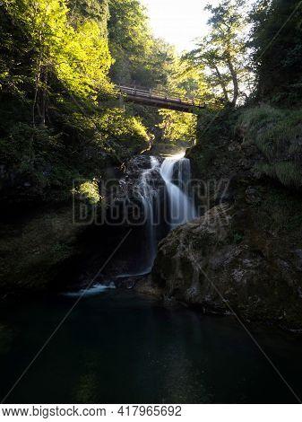 Long Exposure Of Slap Sum Waterfall Bridge, Soft Sun Light At Vintgar Gorge Canyon Radovna River In