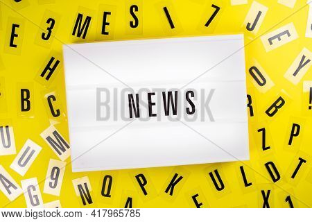 Lightbox With Text Message News On Yellow Background With Black Letters Randomly Scattered. Concept