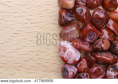 South Onyx Heap Jewel Stones Texture On Half Light Varnished Wood Background. Place For Text.