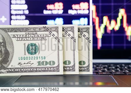 Banknotes On Keyboard Computer. Close Up Of  Banknotes With Trading Exchange Market Price Chart In T