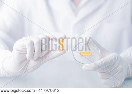 Close Up Scientist Holding Capsule Gel In Labcoat