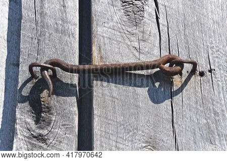 An Old Latch And Key  Are Holding Two Wooden Doors Of Weathered Wood Together