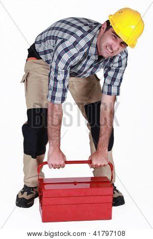 Builder struggling to lift heavy tool box