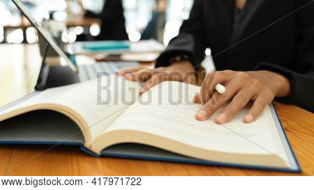 Female Student Reading Textbook To Prepare For Her Coming Exam