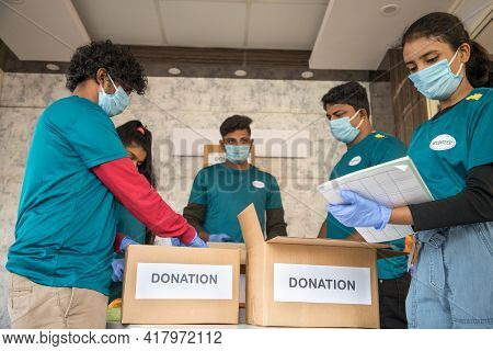 Focus On Front Girl, Group Of Volunteers Busy Working By Arranging Clothes And Donation Boxes During