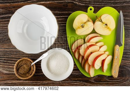 Empty Glass Bowl, Spoon In Bamboo Bowl With Ground Cinnamon, Bowl With Sugar, Pieces Of Apples On Gr
