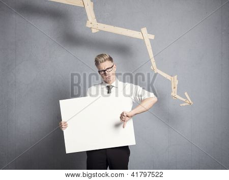 Concept: Business decline. Displeased businessman giving thumbs down at white empty signboard with space for text in front of business graph with negative trend, isolated on grey background. poster
