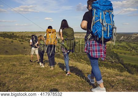 Rear View Of Young Hikers Hiking With Backpacks In Green Summer Field During Summer Vacations