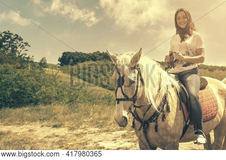 The Rider On The White Horse. Young Horsewoman Riding On White Horse, Outdoors View. Girl On White H