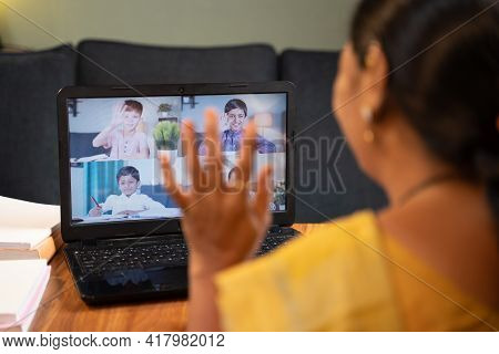 Shoulder Shot Of Teacher, Tutor Greeting Her Students During Online Class - Concep Of New Normal Vir