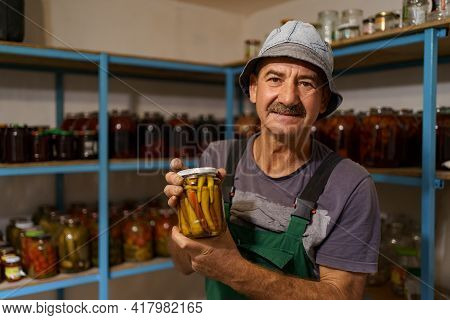 Man Satisfied With The Result Of His Work. He Holds A Glass Jar With Marinated Peppers. Fermented Or